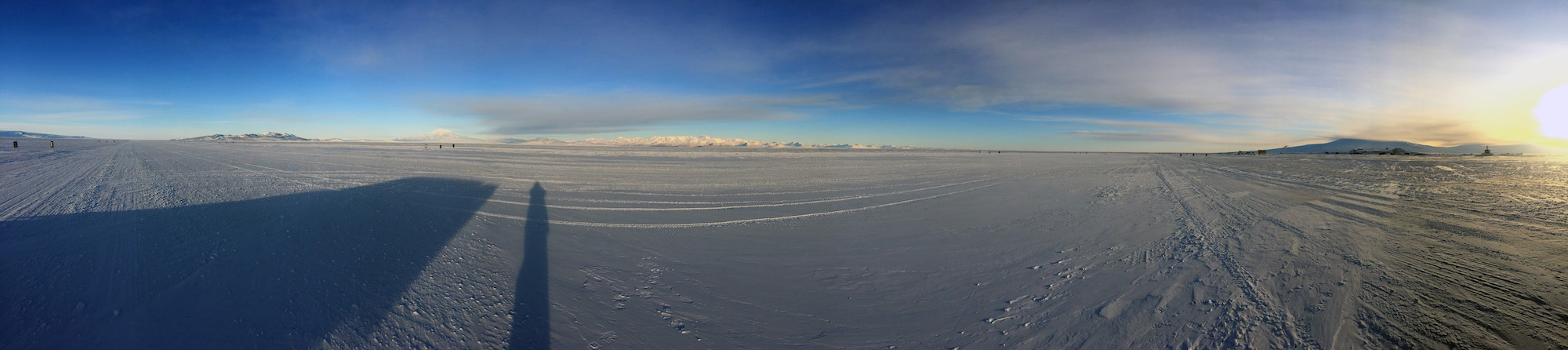 Early morning sun illuminating Black Island, the Transantarctic Mountains, and Ross Island (from left to right).