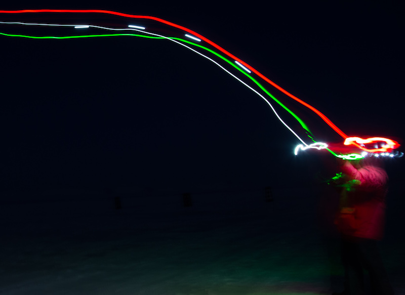 A SUMO launch in the dark. The red, green, and white streaks are the lights on the SUMO captured during the long exposure used to take this photo. (Photo taken by Mark Seefeldt)
