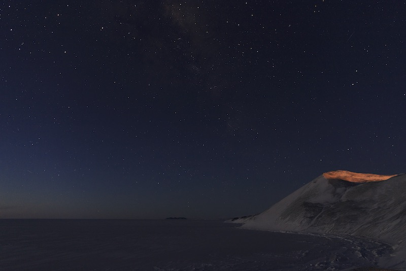 A view of the stars looking north from Hut Point. The next land north from here is New Zealand - over 2000 miles away. In this photograph you can still see a lingering glow on the horizon from the sun that set several hours earlier.