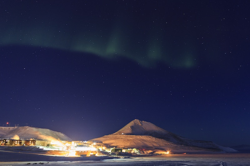 The lights of McMurdo Station under the Southern Lights (aurora australis).