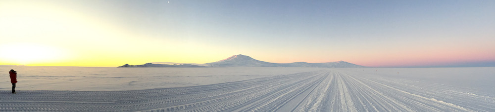 A view of Ross Island at sunset. Mark is standing at the left side of this image and the sun is setting behind the Transantarctic Mountains. Ross Island, with Mt. Erebus, is in the center of the photograph. On the right side of the image you can see the blue shadow of the Earth above the horizon and the pink glow of the sun still illuminating the higher levels of the atmosphere. A thin crescent moon is visible at the top of the image about a third of the way from the left side of the photograph.