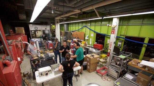 researchers gathered around equipment