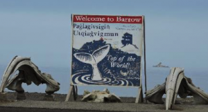 "Bowhead whale skulls alongside the ""Welcome to Barrow"" sign with the Oden sitting offshore in the background at right."
