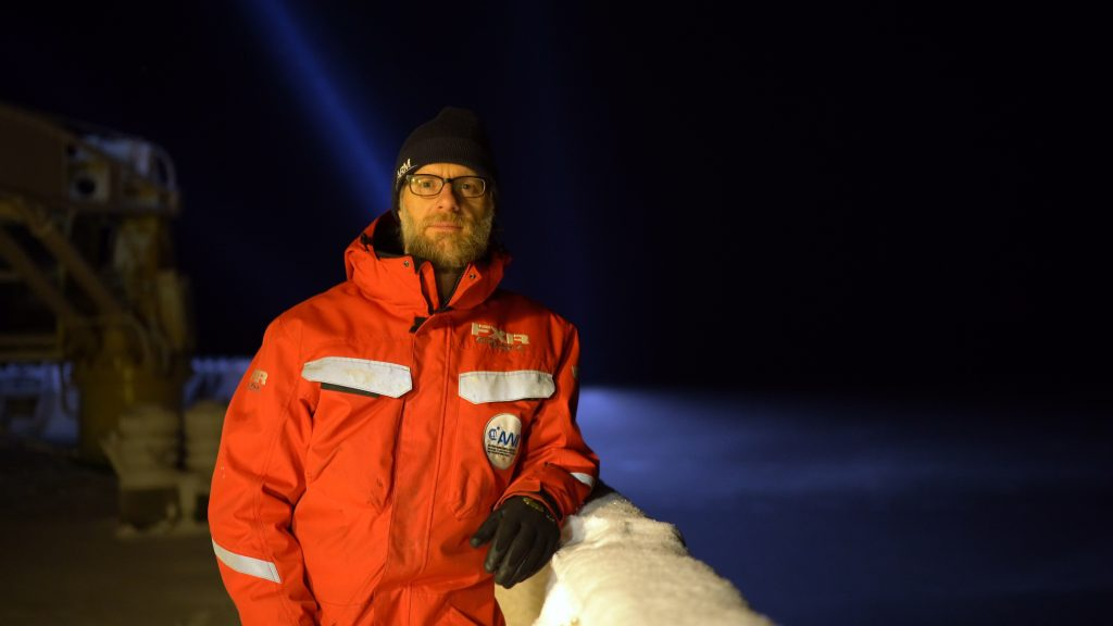 Man stands in orange snow suit on ship at night