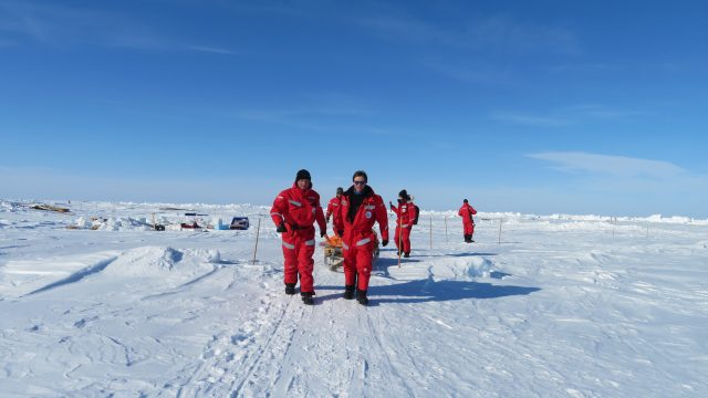 scientists in red walking on ice